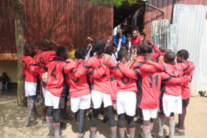 The team huddle up for a pep talk from Coaches Brian and Hussein and Kibera Centre's Director Kariuki.