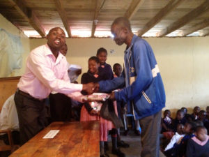 Teacher Obadiah presents a gift to a parent to share with a winning student